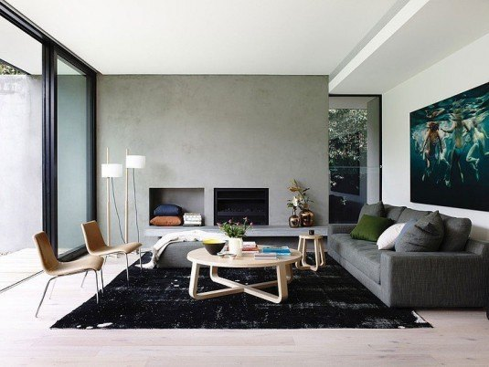 Cozy-living-room-design-with-painting-on-white-walls-equipped-black-fireplace-sofa-cushion-circle-wood-tables-carpets-standing-lamps-lacquered-floor
