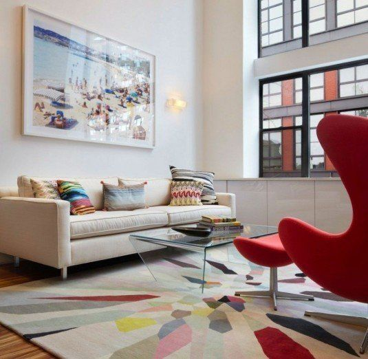 Light-Filled-Duplex-living-area-interior-with-colorful-rug-and-Red-Egg-Chair-also-glass-coffee-table-and-white-comfy-sofa-design-ideas-1024x999