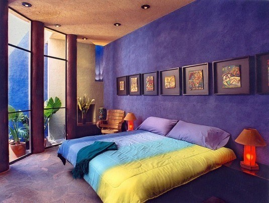 interior-design-for-colorful-bedroom-with-colorful-blanket-and-pillows-also-two-desk-lamps-and-wooden-arm-chair-also-windowed-wall-also-some-paintings-on-frame-also-blue-wall-915x692