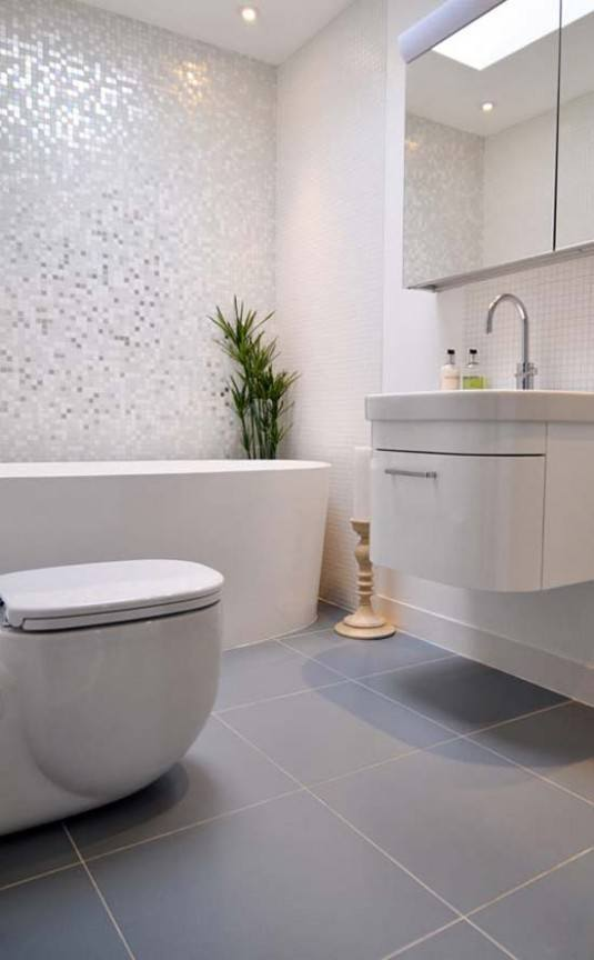 lovely-half-bathroom-design-with-elliptical-fix-bathtub-beside-stylish-white-closet-and-floating-sink-cabinet-vanity-added-with-curved-steel-faucet