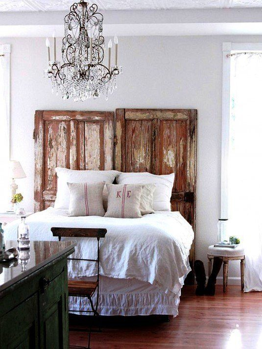 interior-furniture-bedroom-black-iron-mixed-crystal-branched-uplight-chandelier-over-rustic-queen-bed-frame-having-distressed-door-headboard-chandeliers-in-bedrooms